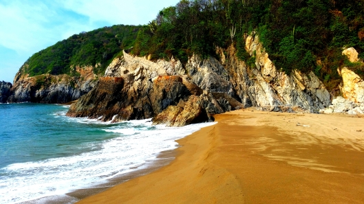 The rocky bluff at the Barra Navidad beach.  If you look carefully you can see stairs leading up over the top and down to another cove.