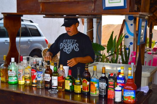 Carlos crafting a new drink behind his tiny street side bar