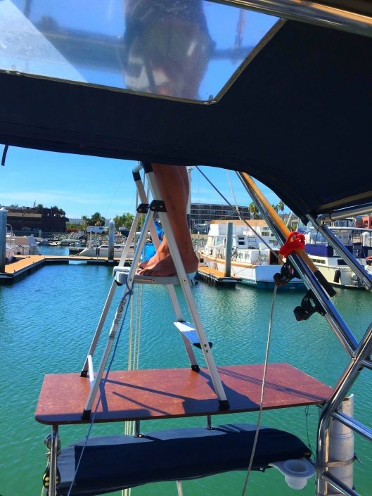 Always improvising.  A stool on top of a door panel on top of the stern seat makes a great ladder.  Good thing the marina was calm!