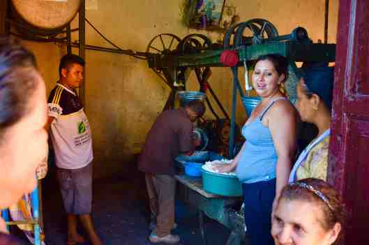 Everyone brings their corn to the town corn grinder.  Her hand is on the finished product, which is then turned into corn tortilla's, etc.