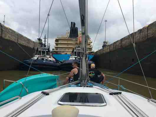 Sereno is secured inside the lock with two tug boats and a ship in front of us.  Austin and Richard will bring in the blue lines on the bow as the water level rises.  Nicki and Anita are on the stern.  Gary is at the helm and I am helping out the gals on the stern.